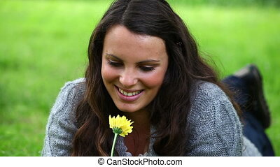Smiling brunette smelling a yellow flower in a park