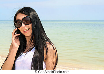 smiling brunette speaking on the phone