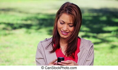 Smiling brunette standing while using her cellphone
