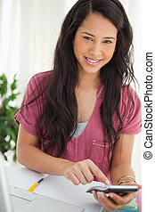 Smiling brunette student using a calculator