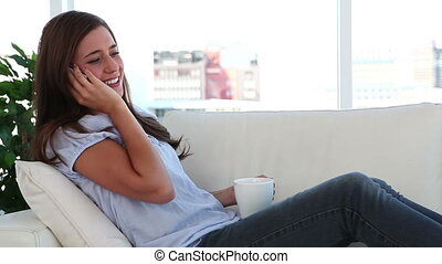 Smiling brunette talking on the phone in the living room