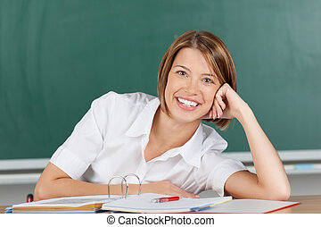 Smiling brunette teacher with hand on her cheek