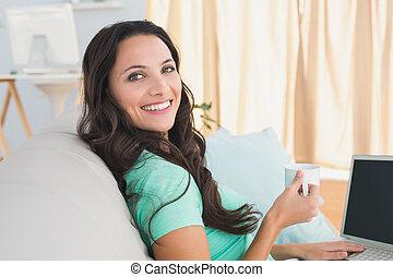 Smiling brunette using her laptop on sofa