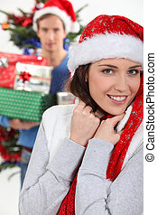 smiling brunette wearing Christmas cap with boyfriend in background at Christmas