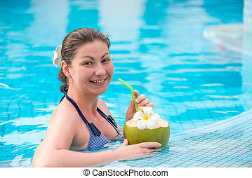 smiling brunette with a coconut resting in a pool in the tropics