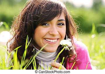 Smiling brunette with dandelion