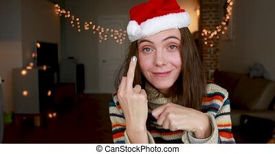 Smiling brunette with loose hair shows middle finger as joke...