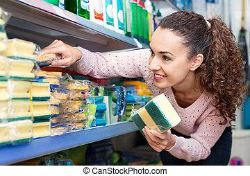 Smiling brunette woman choosing sponges