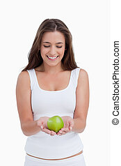 Smiling brunette woman holding a beautiful green apple
