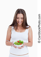 Smiling brunette woman holding a bowl of salad