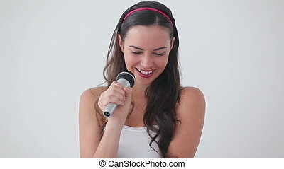 Smiling brunette woman holding a microphone
