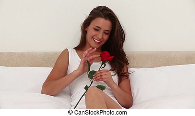 Smiling brunette woman holding a rose