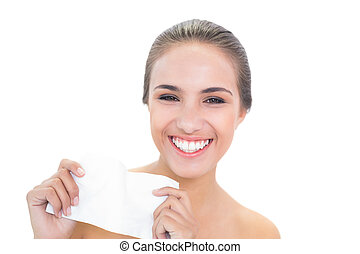 Smiling brunette woman holding a tissue