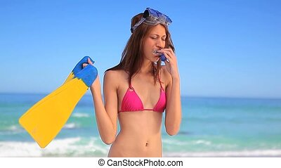 Smiling brunette woman holding a snorkeling equipment on the...
