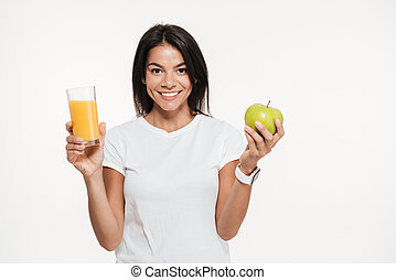Smiling brunette woman holding glass of an orange juice