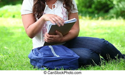 Smiling brunette woman holding notebooks