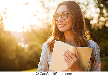 Smiling brunette woman in eyeglasses holding book and looking away