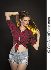 Smiling brunette woman in jeans shorts and plaid shirt