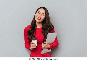Smiling brunette woman in red blouse holding laptop computer