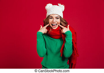 Smiling brunette woman in sweater, funny hat and scarf