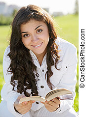 Smiling brunette woman in white with book