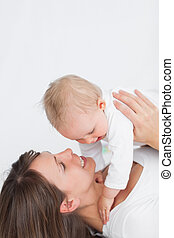 Smiling brunette woman playing with her baby