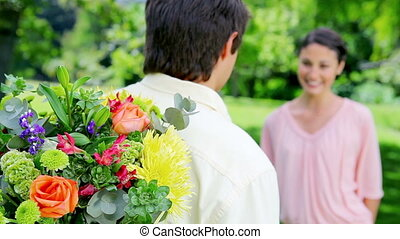 Smiling brunette woman receiving a bunch of flowers in a...