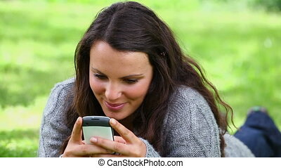 Smiling brunette woman sending a text message