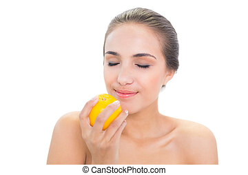 Smiling brunette woman smelling on an orange
