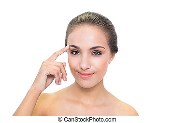 Smiling brunette woman touching her eyebrow