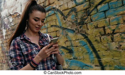 Smiling brunette woman using a smart phone walking in the street at sunny day