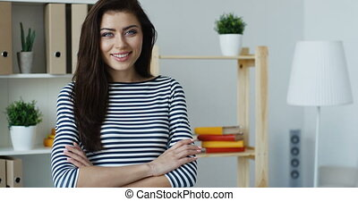 Smiling brunette woman wearing striped blouse crossing...