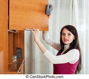Smiling brunette woman wiping the dust