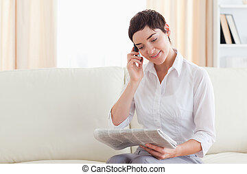 Smiling brunette Woman with a cellphone and a newspaper