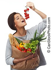 Smiling  brunette woman with grocery bag full of fresh vegetables and cherry tomatoes