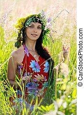 Smiling brunette woman with long black hair sitting in grass with wreath on her head in summer meadow