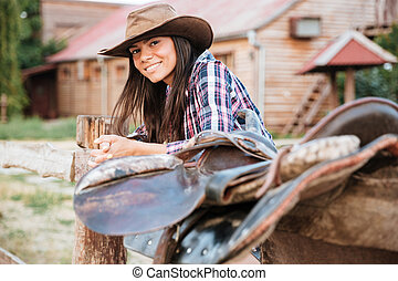 Smiling brunette young woman cowgirl leaning on fence in...