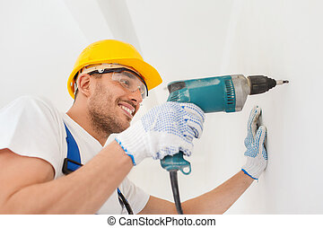 smiling builder in hardhat drilling wall indoors - building,...