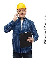 smiling builder in helmet calling on smartphone - repair, ...
