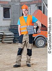 Smiling builder keeping toolbox