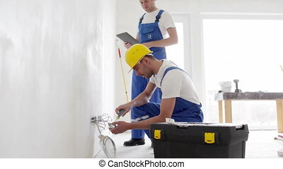 smiling builders with tablet pc and equipment