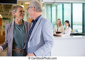 Smiling Business Couple Looking At Each Other In Airport