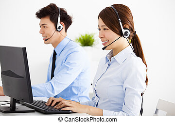 smiling business man and woman with headset working in office