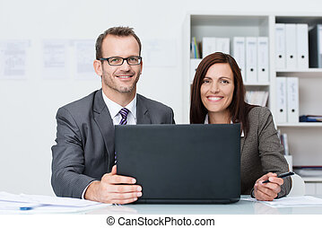Smiling business man and woman working together