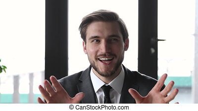 Smiling business man coach talking to camera during online training webinar course. Happy young confident businessman speaking making job interview conference video call in office, recording ad promo.