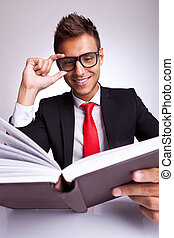 business man fixing his glasses while reading