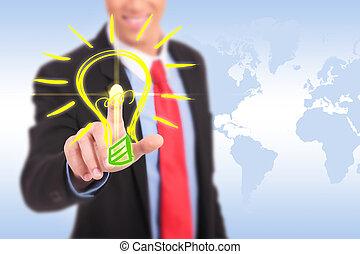smiling business man pushing a light bulb button