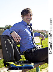 Smiling business man relaxing sitting on banch