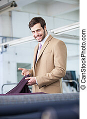 smiling business man showing textile material