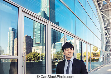 smiling business man standing in front of office building